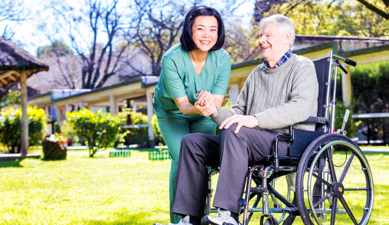 senior man and female caregiver smiling
