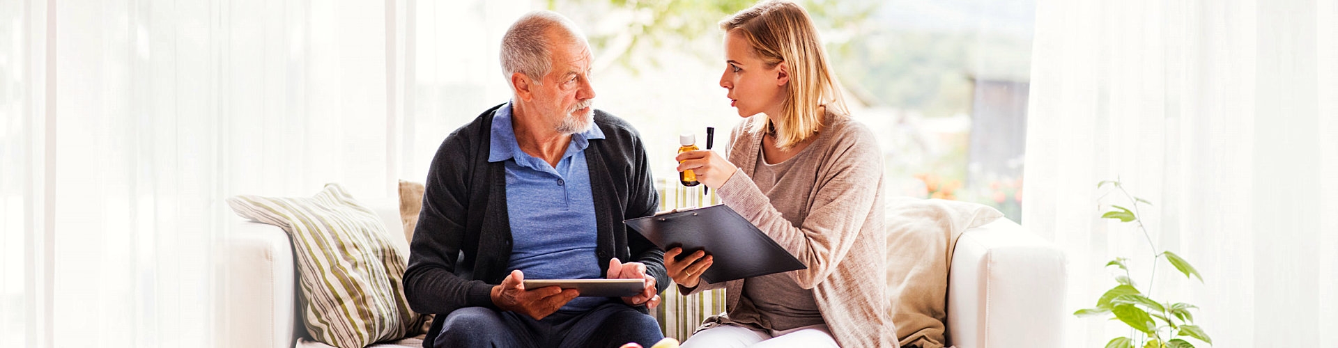 female caregiver and senior man looking at each other