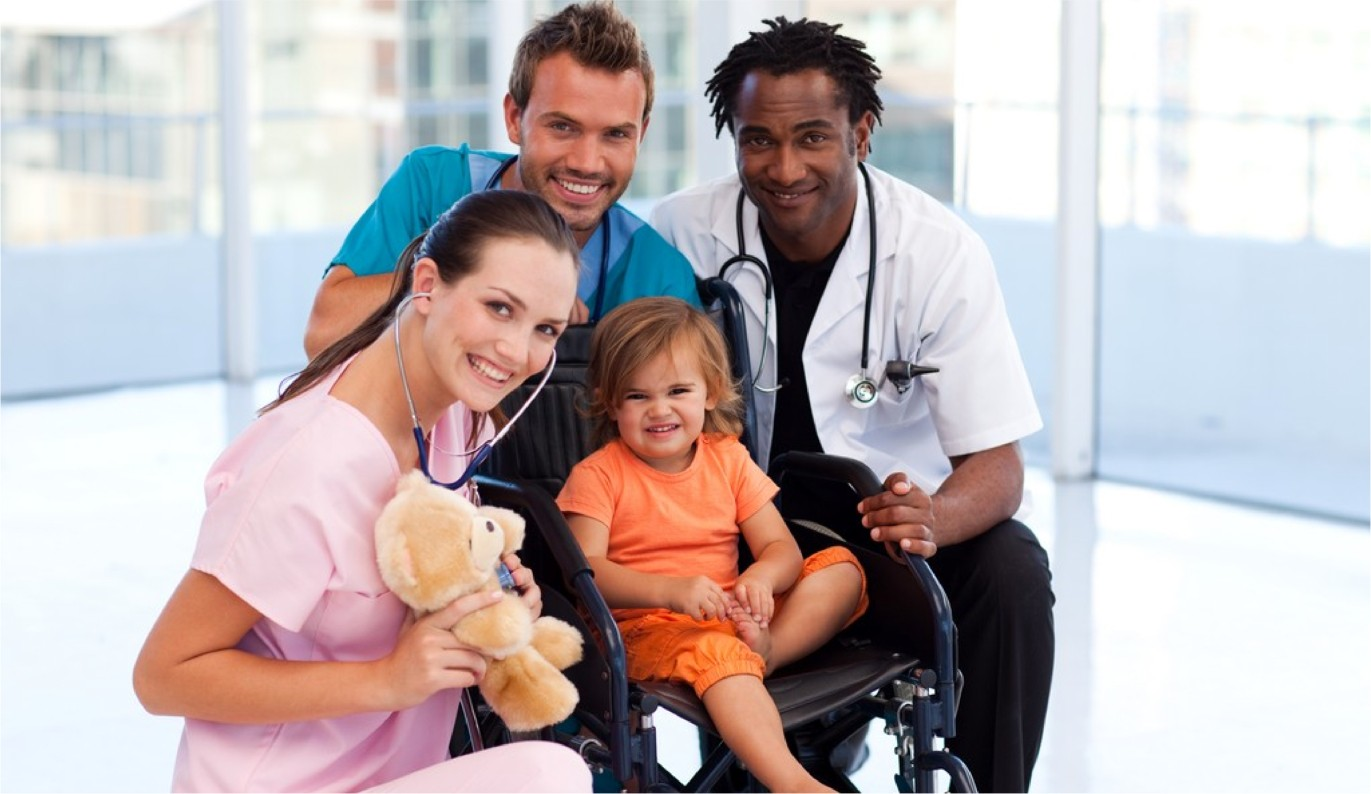 Little patient with medical team in a wheelchair smiling at the camera