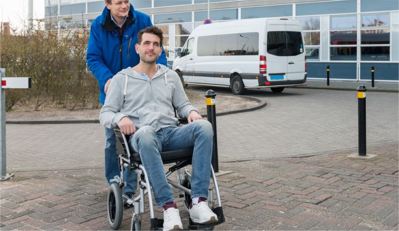 Happy father pushing son on wheelchair with van in background