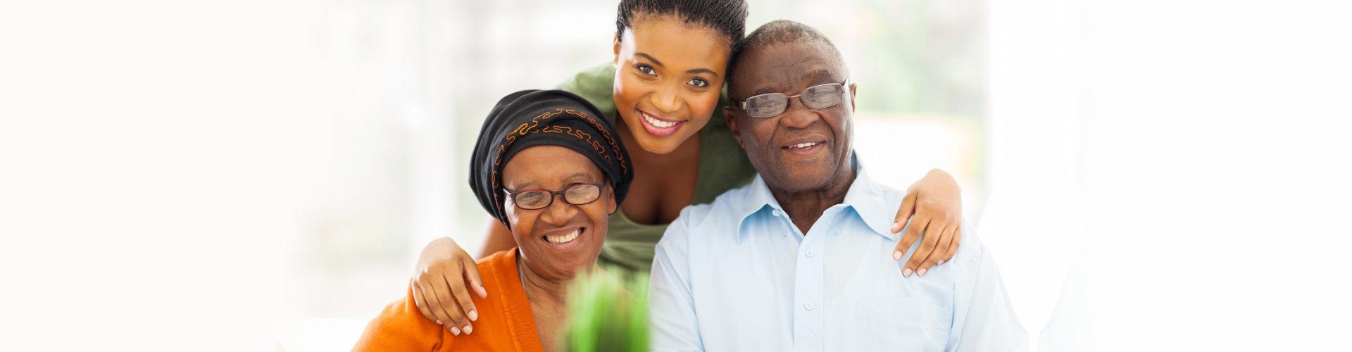 senior couple and female caregiver smiling