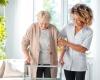 caregiver assisting senior woman with walker
